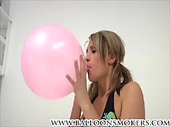 Teen blows to pop pink balloons